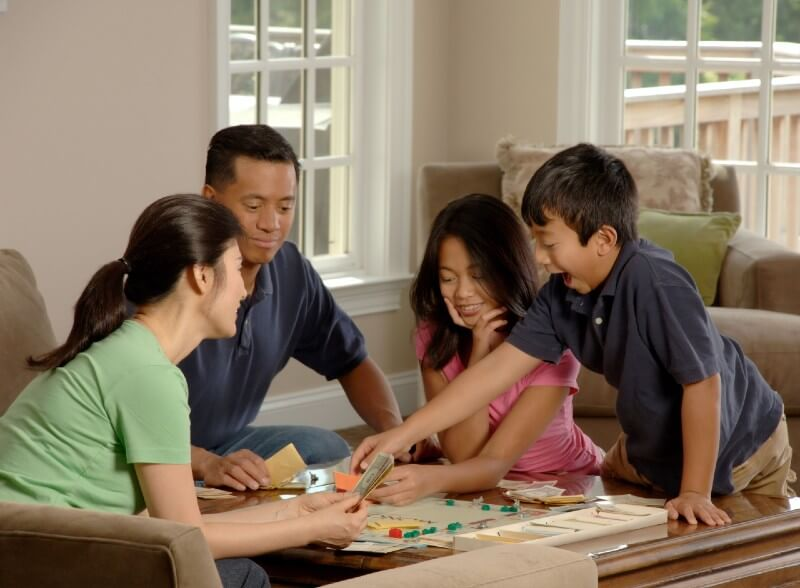 Family playing Monopoly with kids